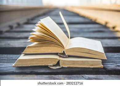 Two old retro vintage aged used book lie on wooden sleepers of railway between metal fence of grunge style bridge on blue sky background Education development cultivation symbol sign concept