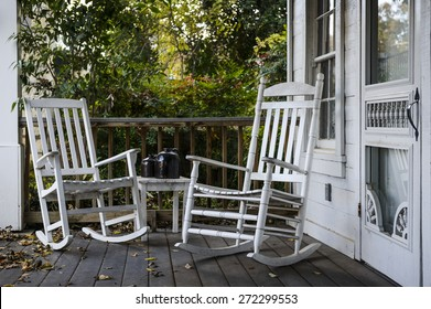 two old rocking chairs on the front porch of an old house
