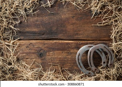 Two old rusty horseshoes surrounded by straw on vintage wooden board