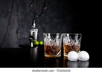 Two old school retro whiskey glasses with scotch and  ice on the table with dark background.