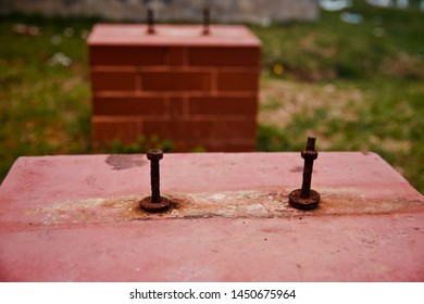 Two of old screws on a red concrete surface