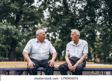 Two old senior adult men have a conversation outdoors in the city park