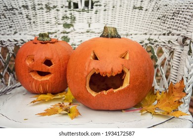 Two old and shriveled pumpkins carved into jack-o-lanterns for Halloween