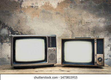 Two old television on wood table with old concrete wall background. Vintage TV filter tone. Retro style