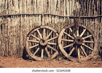 Two old wagon wheels near the wooden fence. Old cart wheel as a symbol and concept of fortune and fate, filtered with soft pastel colors with filters.