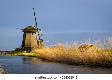 Two old water mills beside a canal of the Eilandspolder in evening light, The Netherlands