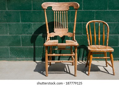 Two old weathered and broken wooden chairs for an adult and a child against a green brick wall.