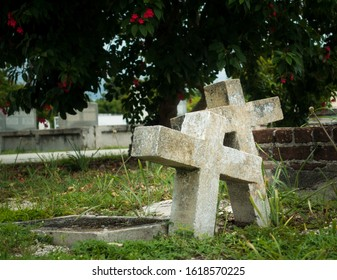 Two old and weathered christian gravestones leaning together on churchyard as sign of eternal love. Grass surrounding graves on churchyard, tree leafs hanging above. No people, daytime shot.