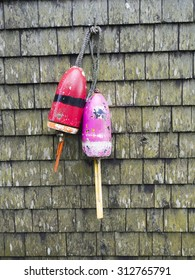 Two old, weathered lobster buoys hanging on the cedar shake wall of an old lobster shack in Maine.