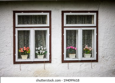 Two old windows on a house with flowers.