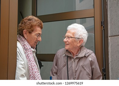 Two old women exiting from a front door talking to each other.