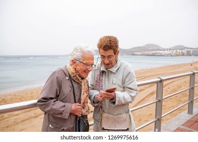 Two old women looking a smartphone screen.