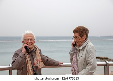 Two old women talking with a cellphone and smiling.