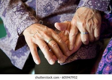 Two old women wrinkled hands touches together.