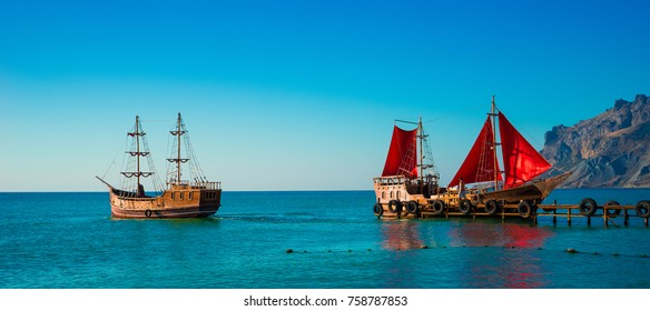 Two old wooden ships. One of them with red sails is on the pier. Scarlet sails, as in the famous story of Alexander Green. The second sails from the pier without raised sails. Koktebel, Crimea.