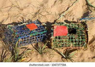 Two old and worn-out, hand made of iron and coloured plastic parts, crab traps washed away by tides and waves into the sand dunes. Vila Nova de Milfontes, Portugal.