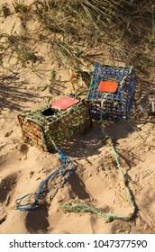 Two old and worn-out, hand made, crab traps washed away by tides and waves into the sand dunes. Iron and colored plastic materials. Vila Nova de Milfontes, Portugal.