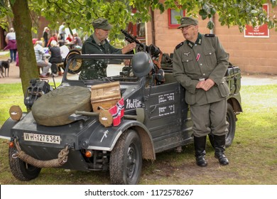 Two older men dressed up in uniforms of Nazi officers. The first is based on the vehicle and the other checks a machine gun mounted on the car. Cannock Chase military history weekend 18-19.08 UK