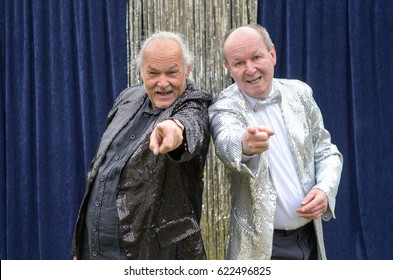 Two older men giving a lively stage performance standing shoulder to shoulder laughing and pointing at the camera