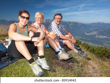 Two older parents with their daughter on top of a mountain