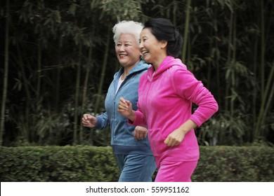 Two older women jogging together