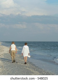 Two older women walking side by side on sandy beach
