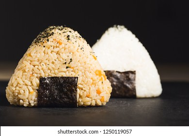 Two onigiri sushi triangles of yellow and white rise, placed on black surface and viewed from the side