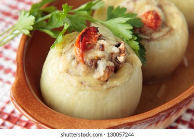 Two onions stuffed with mushrooms, tomatoes and minced meat