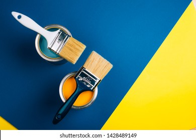 Two open cans with brushes on them on yellow and blue background. Yellow and turquoise colors of paint. Flat lay style. Renovation concept.