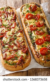 Two open casserole sandwiches with bacon, mushrooms, tomatoes and cheese close-up on the table. vertical