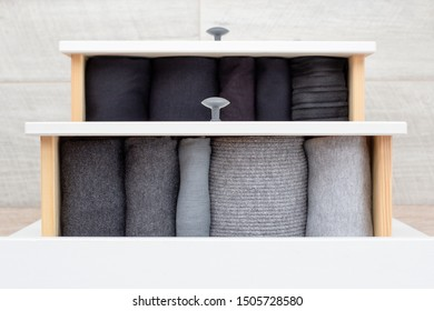 two open drawers with women's clothing in black and different shades of gray of cotton and wool folded in neat piles, top view