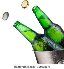 Two open green beer bottles with drops