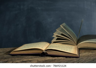 Two open old books on an old wooden table. Beautiful background.