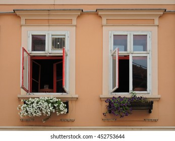 Two opened windows with flowers
