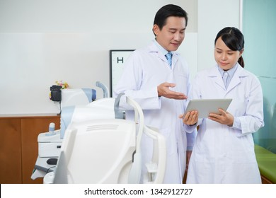 Two ophthalmologists, man and woman, standing in white coats and discussing using digital tablet in their work in ophthalmology clinic