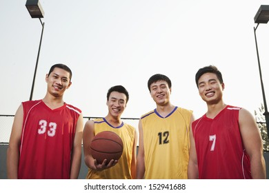Two opposite basketball teams standing and smiling, Portrait
