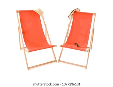 Two orange deckchairs next to each other with a straw hat hanging from each and sunglasses on one chair. Space for text.