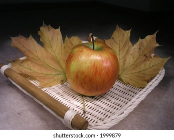 Two orange maple leaves and apple in scuttle