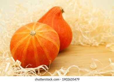 Two orange mini pumpkins on a wooden board. Wood shavings around the pumpkin. Place for text. Autumn background.