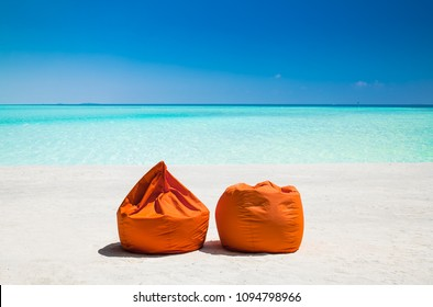 Two  orange pellet bean filiing ban at mazing vibrant beach with turquoise water on Olhuveli island, Maldives.