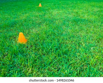 Two orange plastic cones equipment used in outdoor fitness workout exercises.