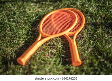 Two orange tennis rackets lying on the grass