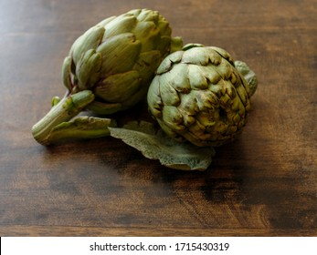 Two organic fresh artichokes on a dark brown wooden background .