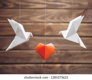 Two origami dove birds around red paper heart on wooden background. Greeting card for Valentines day.