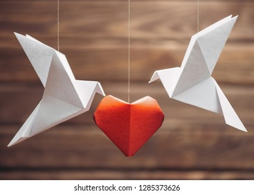 Two origami dove birds around red paper heart, symbol of love. Greeting card for Valentines day.