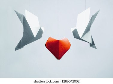 Two origami dove birds around red paper heart on white background. Greeting card for Valentines day.