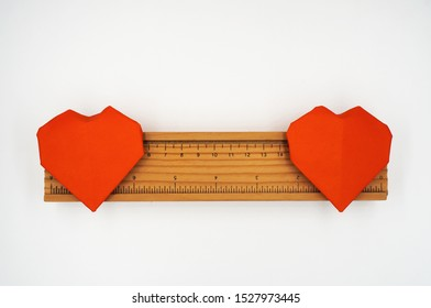 Two origami paper heart on wooden ruler on white background , love distance relationship concept