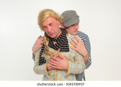 Two original guys hug. One in a cap and in a vest, and the second in a jacket and a yellow wig.