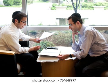 two Orthodox Jewish undergraduate college students working on a class assignment together during a break between classes,  in a campus lounge, Queens, NY, USA, May 9, 2016