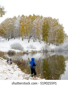Two other anglers - one crouching, another standing on the shore of the lake with the snow and grass. Soft focus.  Soft focus.
